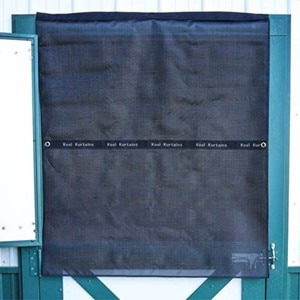 A black Kool Kurtain covering a horse's open top stall door to help reduce sun exposure.